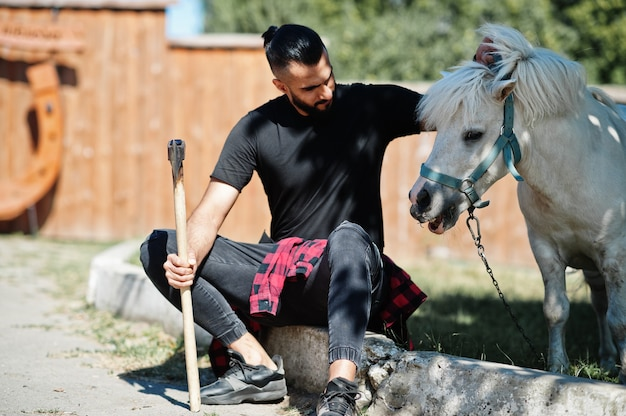 Arab hipster beard man lumberjack hold axe against pony horse