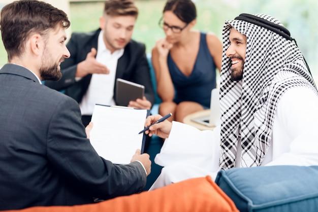 아랍인은 펜을 들고 서명을 기다립니다.