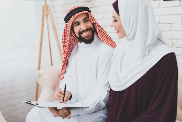 Arab husband smiles to wife signing contract.