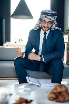 Arab looking at wrist watches with cup of coffee.