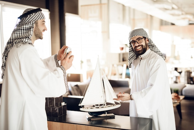 Arab making photo with ship model for friends