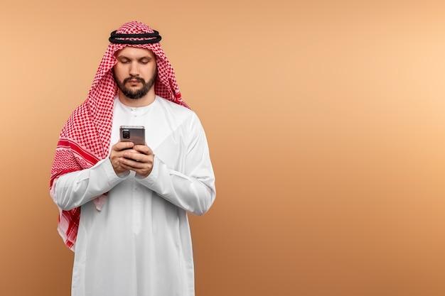 民族衣装を着たアラブ人のビジネスマンが、ベージュの壁にスマートフォンを手に持つ。