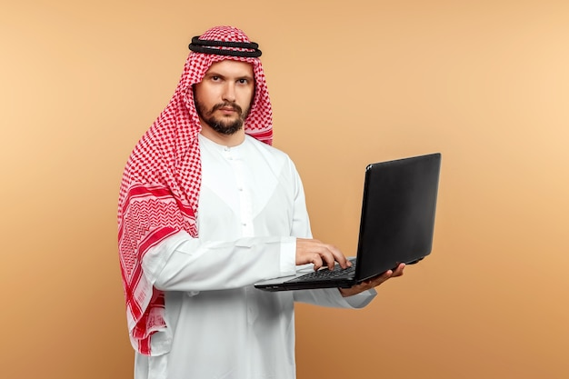 An arab man, a businessman, a sheikh works at a laptop. investments, business, work via the internet, online contracts.