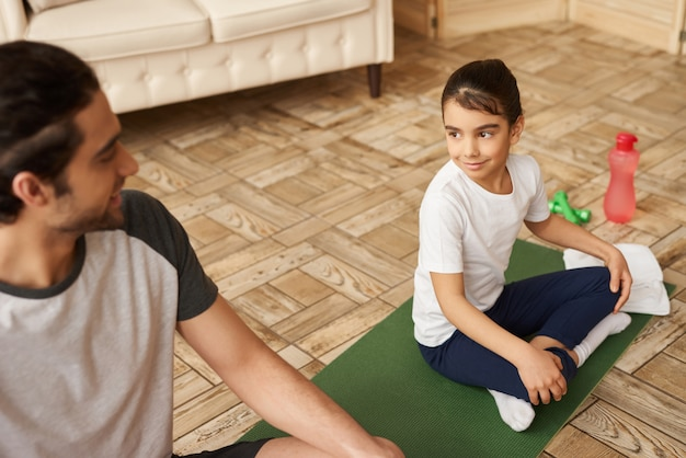 Arab man and girl are doing exercises at home.
