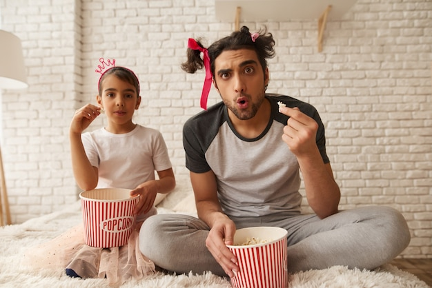 Arab man and girl are eating popcorn in the bed.