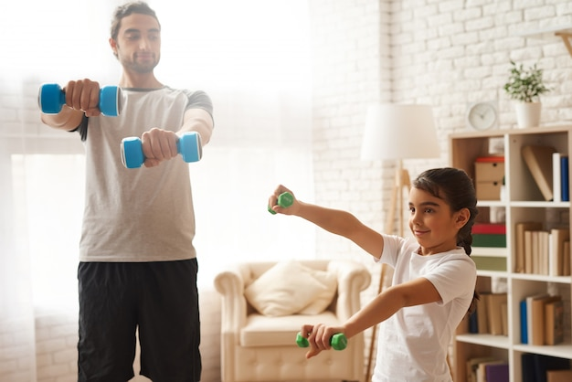 Arab man and girl doing exercises with dumbbells