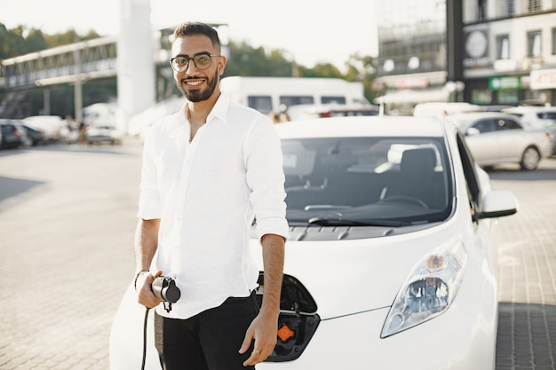Arab man holding electric car plug. smiling at camera, standing in the city near electro car.