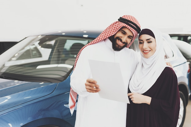 Arab man holds car contract gift for happy woman.
