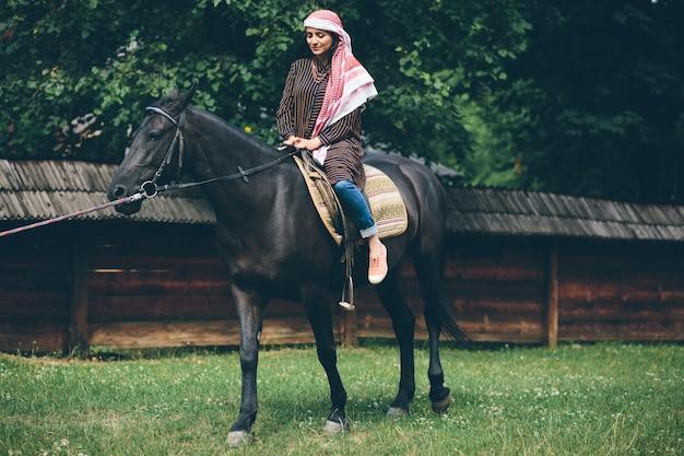 馬に座っている黒い服を着たアラブ人