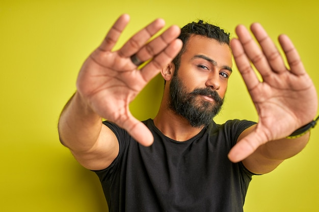 Arab man is making frame with hands and fingers with confident face, young male