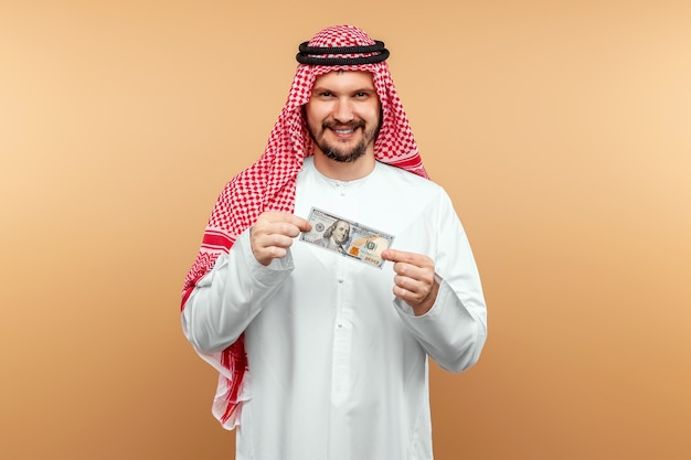 An arab man in a national costume holds dollars in his hands.