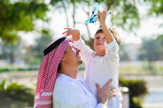 Arab man in traditional dress holds his son and play with toy plane.
