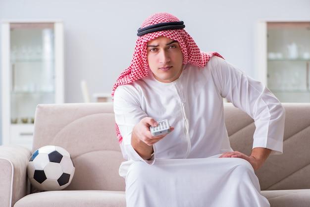 Arab man watching sport football at tv