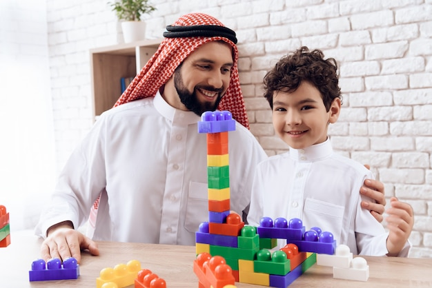 Arab man with boy builds tower of colored plastic blocks.