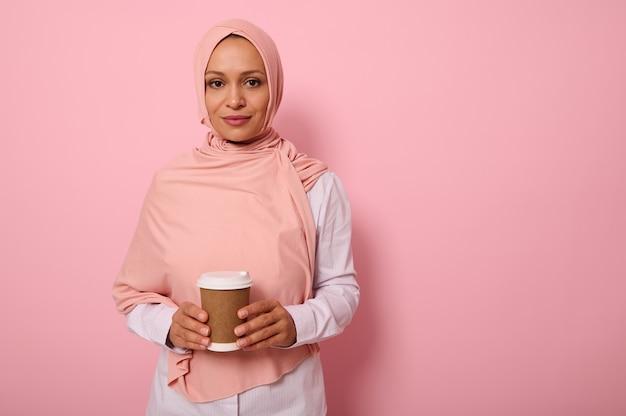 분홍색 히잡과 흰색 셔츠를 입은 아랍 이슬람 아름다운 여성은 손에 재활용 가능한 생태 종이 머그잔을 들고 카메라를 바라보며 복사공간이 있는 색색의 배경에 격리되어 있습니다.