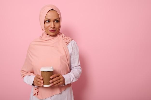 분홍색 히잡과 흰색 셔츠를 입은 아랍 이슬람 아름다운 여성이 손에 재활용 가능한 생태 종이 머그잔을 들고 복사 공간이 있는 유색 배경에 포즈를 취하고 있는 측면을 바라보고 있습니다.