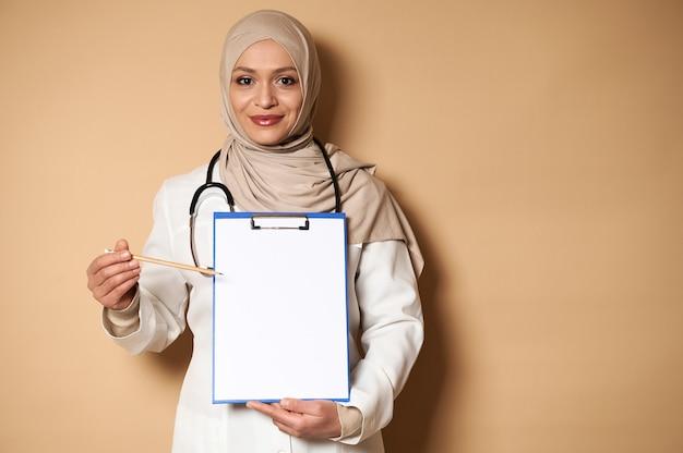 クリップボードの白紙に鉛筆で指しているヒジャーブのアラブのイスラム教徒の医師