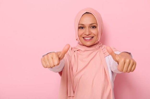 ピンクのヒジャーブのアラブのイスラム教徒のフレンドリーで魅力的な女性は、カメラに向かって親指を示し、歯を見せる笑顔で笑顔、コピースペースで色付きの背景の上に分離