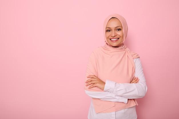 ヒジャーブの交差する腕を身に着けているアラブのイスラム教徒の女性は、美しい歯を見せる笑顔で笑って、カメラを見ているコピースペースでピンクの背景にポーズをとる。成功した自信のあるイスラム現代女性の概念