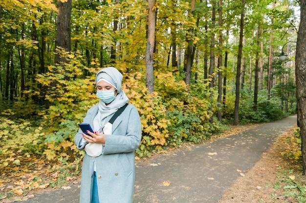 屋外でコロナウイルスから身を守るためにフェイスマスクを身に着けているアラブのイスラム教徒の女性