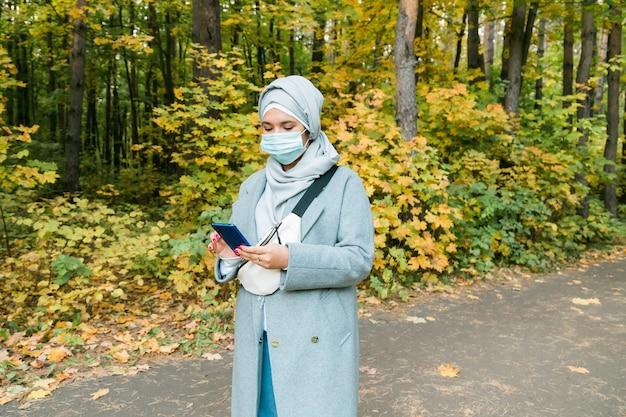야외에서 코로나바이러스로부터 자신을 보호하기 위해 얼굴 마스크를 쓴 아랍 이슬람 여성