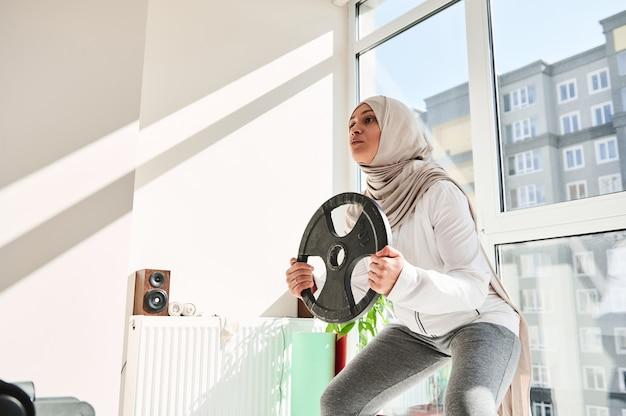 彼女の手に金属ディスクで加重スクワットをしているヒジャーブを身に着けている頭飾りを持つアラブのイスラム教徒の女性