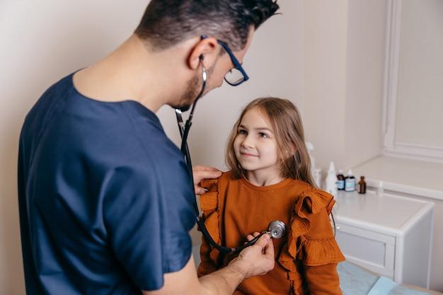 Арабский или турецкий педиатр слушает легкие маленькой девочки. фото высокого качества