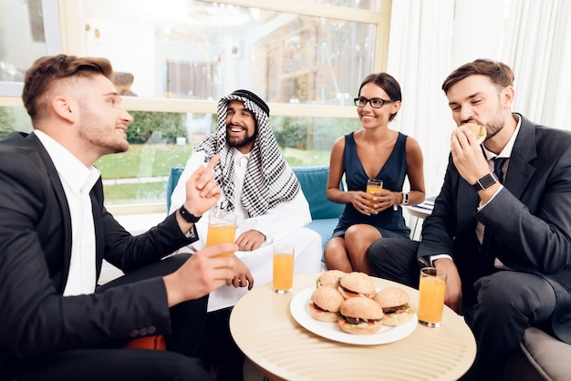 Arab and other businessmen are eating burgers.