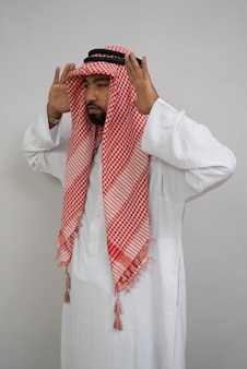 Арабские люди в тюрбане молятся во время итидаля с двумя руками рядом с головой
