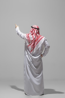 Una persona araba che propone vista posteriore isolata su studio grigio