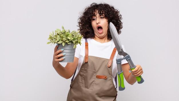 剪定ばさみを持つアラブのきれいな女性の庭師