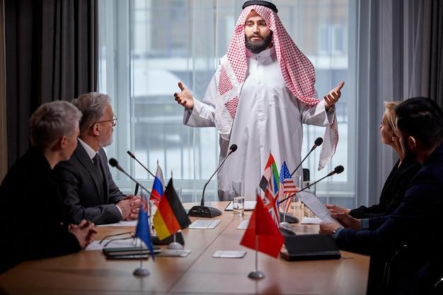 Арабский шейх проводит встречу без галстуков для обсуждения идей и вопросов повестки дня, используя микрофон для выступления. в зале заседаний собрались многоэтнические коллеги