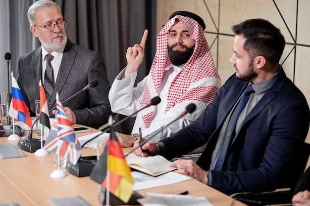 Arab sheikh holds a meeting without ties to discuss ideas and issues on the agenda, using microphone for giving speech. in boardroom, multi-ethnic colleagues gathered together