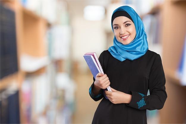 그의 팔에 책을 들고 도서관에 서 있는 아랍 학생. 교육 개념입니다.