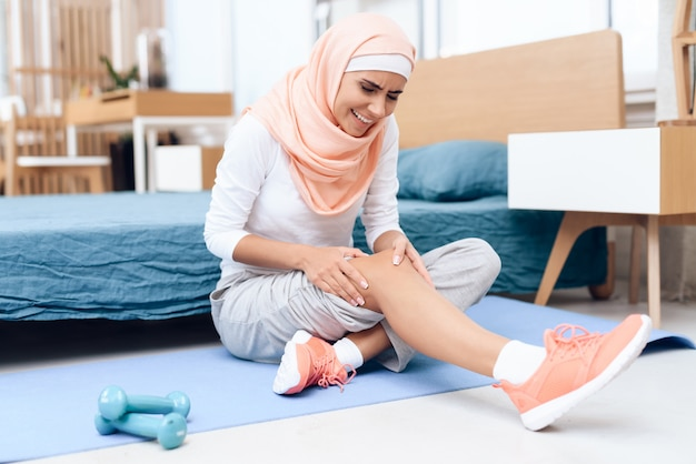 Arab woman doing gymnastics in the bedroom.