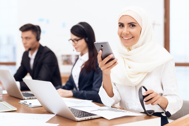 An arab woman in a hijab looks at the phone.