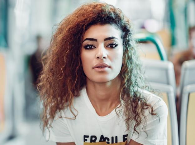 地下鉄の列車の中のアラブの女性。カジュアルな服装のアラブの女の子