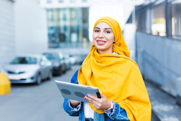 Arab woman student. beautiful muslim female student wearing bright yellow hijab holding digital