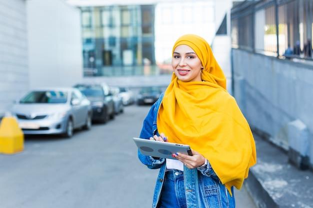 Arab woman student. beautiful muslim female student wearing bright yellow hijab holding tablet