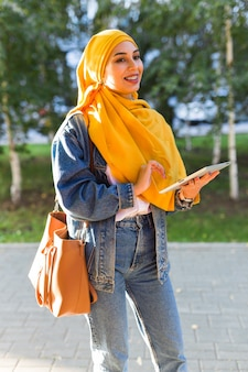 Arab woman student. beautiful muslim female student wearing bright yellow hijab holding tablet.
