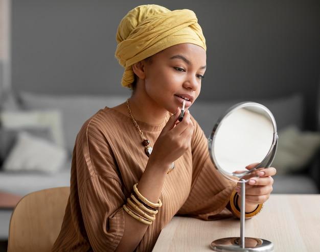 립스틱을 사용하는 아랍 여자. 미용 치료