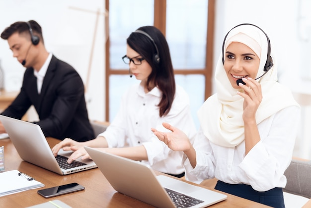 An arab woman works in a call center.