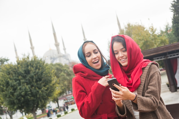 Arab women wearing veil using a smart phone in istanbul