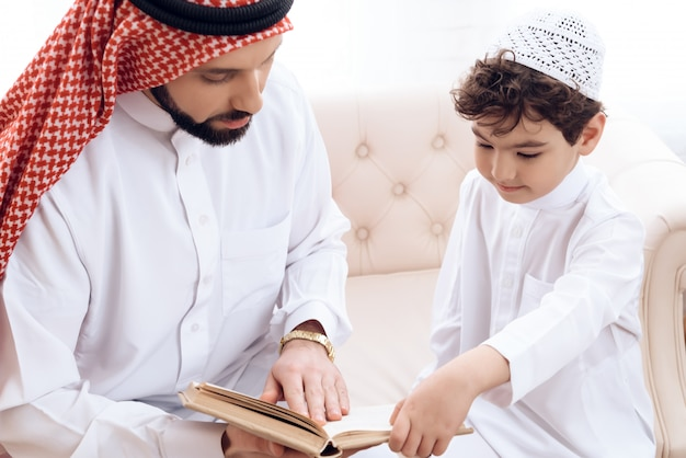 Arabian bearded man is reading book with small son.