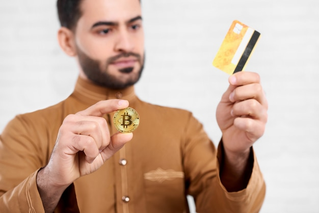 Arabian businessman keeps golden bitcoin in one hand and golden credit card in another. he wears beige shirt with a pattern. close-up was made on the white studio background.