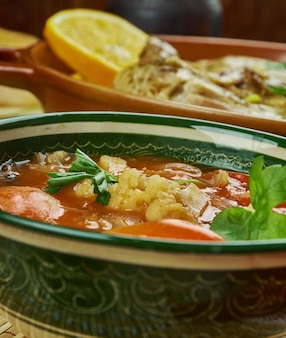 Arabian cuisine - shurba omani, omani vegetable soup, traditional assorted  dishes, top view.