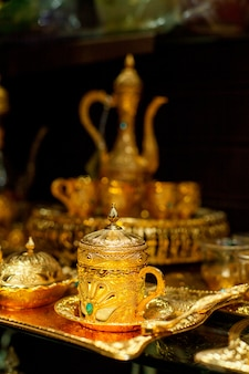 Arabian cup and teapot of gold on the eastern market. oriental tea