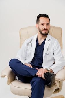 肘掛け椅子に聴診器の座席を備えた医療用ローブのアラビア医師外科医 Premium写真