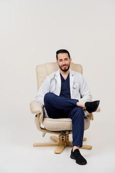 肘掛け椅子に聴診器の座席を備えた医療用ローブのアラビア医師外科医