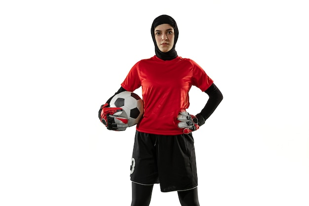 Arabian female football player, goalkeeper on white studio wall